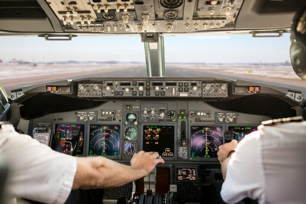 Captain is pulling an aircraft throttle, while first officer is piloting and taking off. Pilots are sitting in Boeing 737-800.